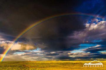 wunderschöner Regenbogen über dem Gästehaus Langaholt, Island